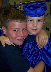 ben graduating from preschool in his cap and gown, being hugged by his brother